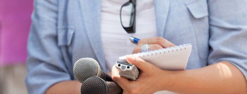 Journalistin mit Mikrophon und Block